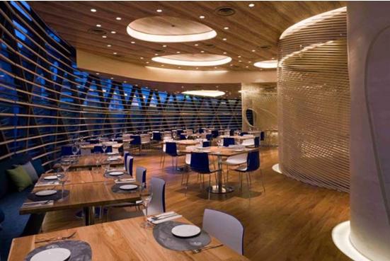 线性平面划分和布局;开间方向流动相的座椅和餐桌,与流动型的镂空隔断形成了一个整体,造型增强了空间的亲密氛围。木色木条作为室内墙面的主要材料奠定了整个空间的基调,而整个西餐厅桌椅和配饰运用了不同程度的灰色,营造出一种神秘的氛围。这就是特色餐厅装修设计的魅力!